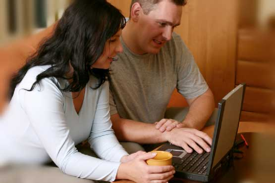 Happy couple working on laptop